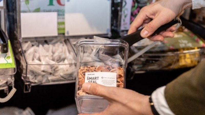 An image of the PG Tips refill station, with a customer using a reusable container.