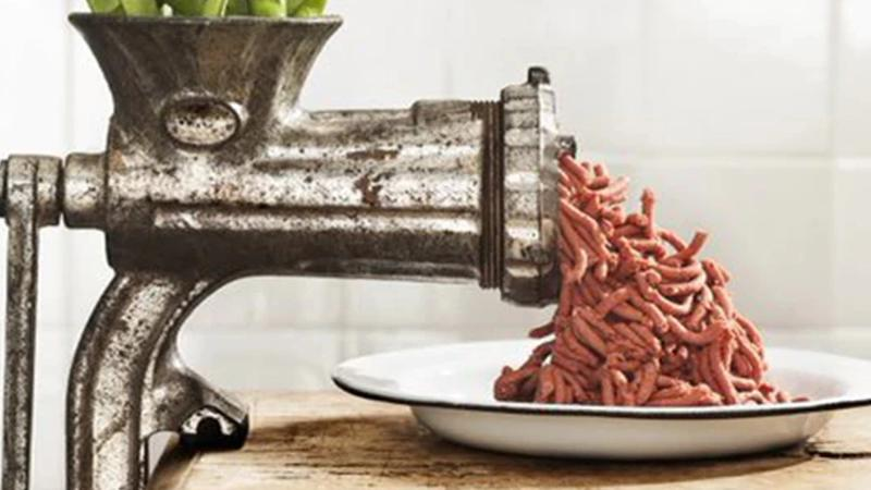 Meat grinder: vegetarian minced meat coming out of a metal meat-grinder
