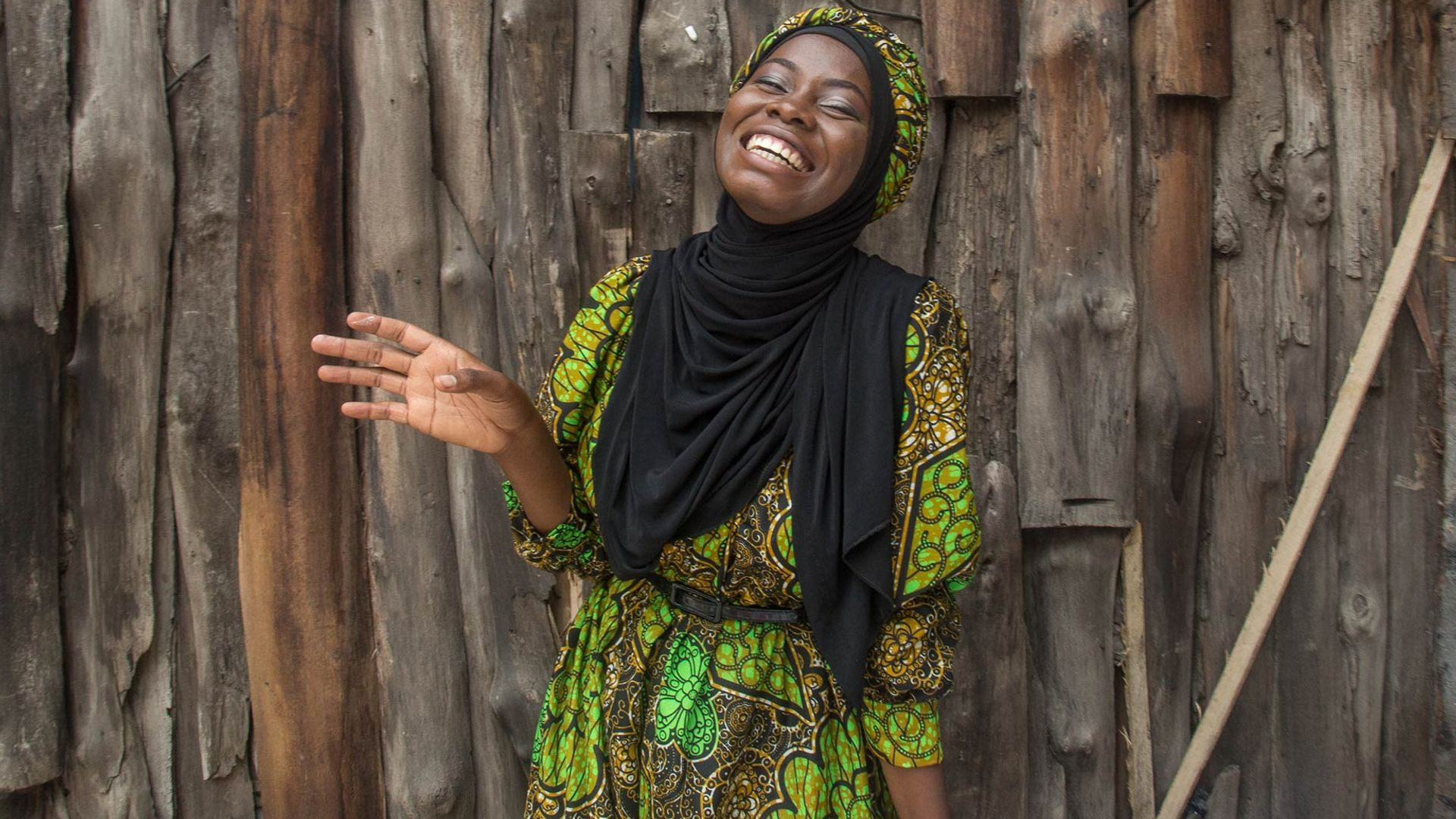 A woman standing beside a wooden fence and smiling