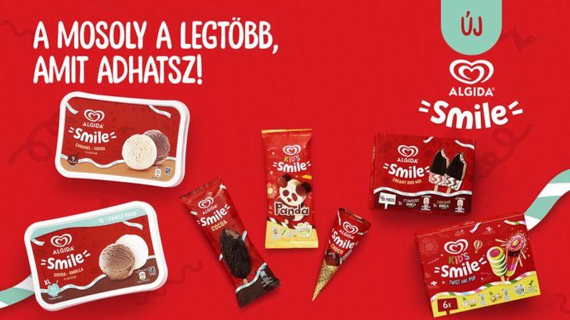 """Piros háttéren Algida Smile termékek: dobozos fagyi, jégkrém, 6-os csomag. Felirat: """"A mosoly a legtöbb, amit adhatsz!"""""""
