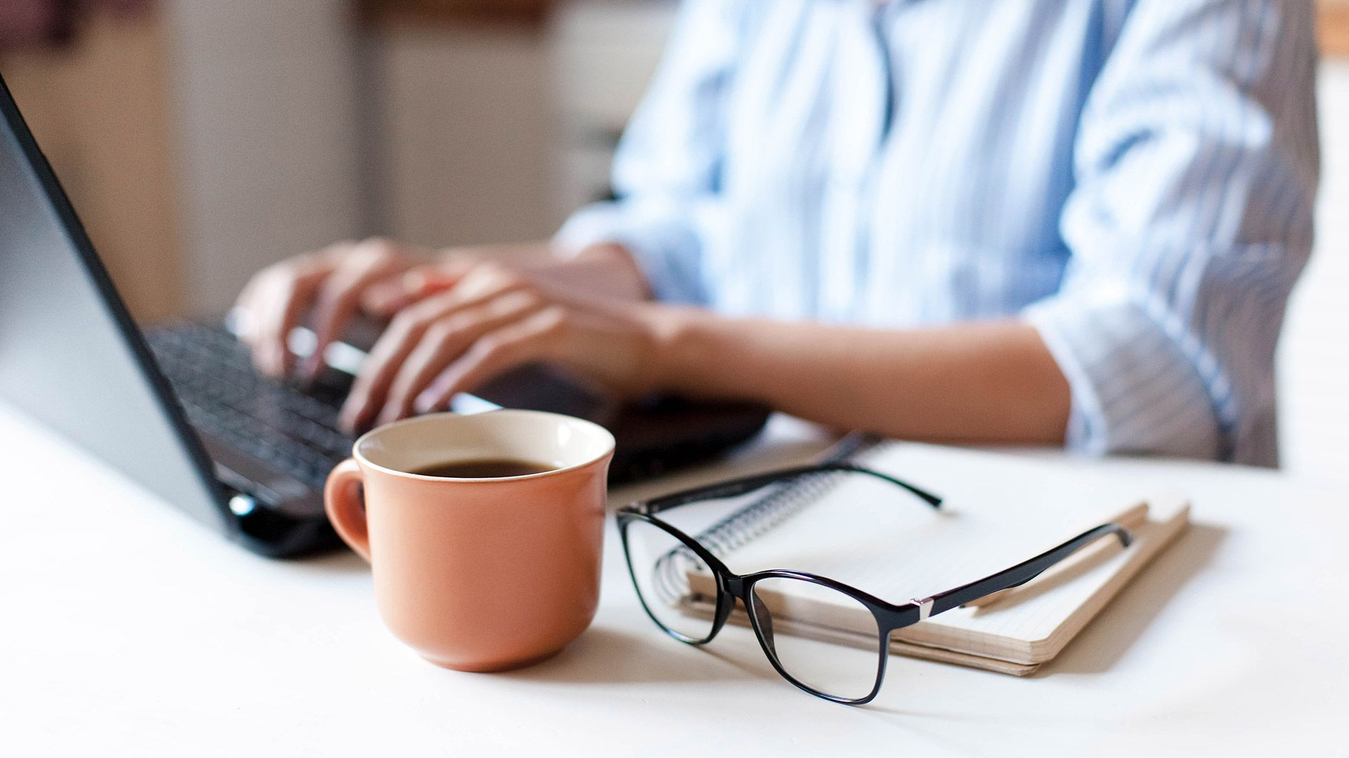 a close up of hands at a laptop with a pair of glasses and a cup of coffee in the foreground