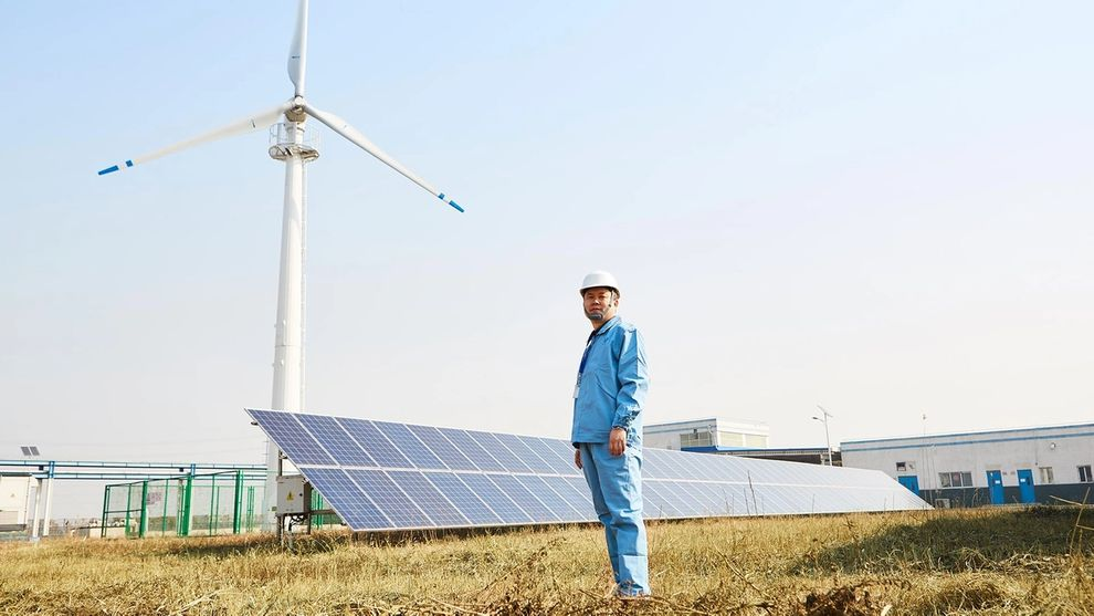 Man standing in front of solar panels and wind turbines at Unilever China factory