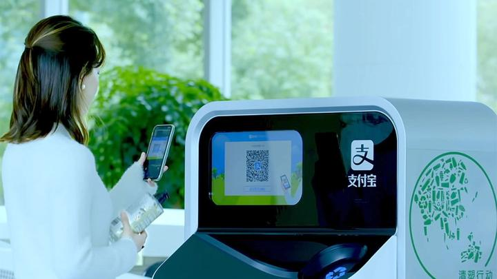 Woman holding plastic bottle ready to scan its QR code into an AI-enabled recycling and sorting machine