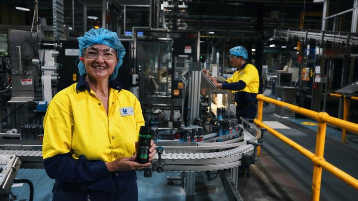 Unilever employee holding can of Lynx deodorant in factory