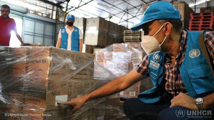 UNHCR volunteer sorting through pallet of Rexona deodorants