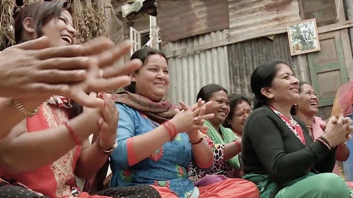 A group of South Asian women in colourful clothes sit on the floor smiling and clapping