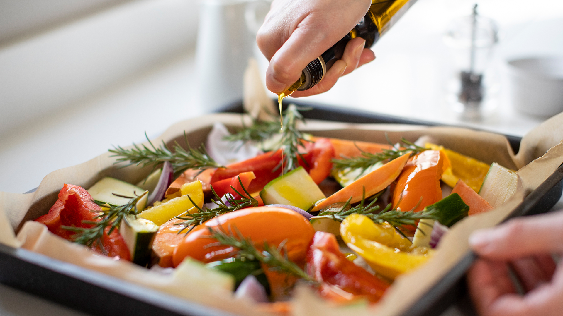 A person pouring olive oil over a roasting pan full of vegetables