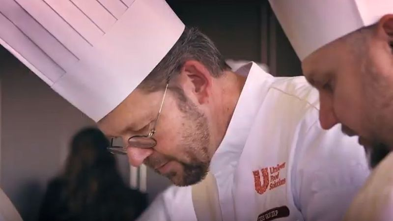 A man wearing glasses, a chefs hat and chef whites featuring the Unilever Food Solutions logo