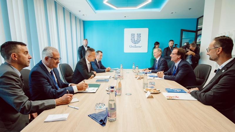 Tárgyalóasztal körül öltönyben beszélgetnek