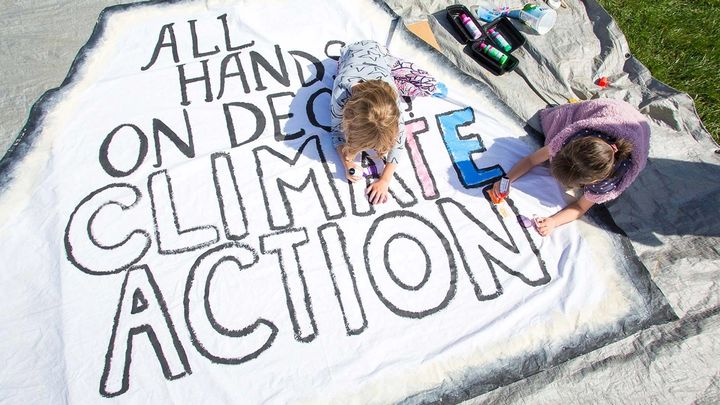Two girls colouring in an 'All hands on deck climate action' poster