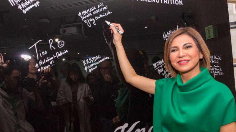 Woman with green dress signing the board