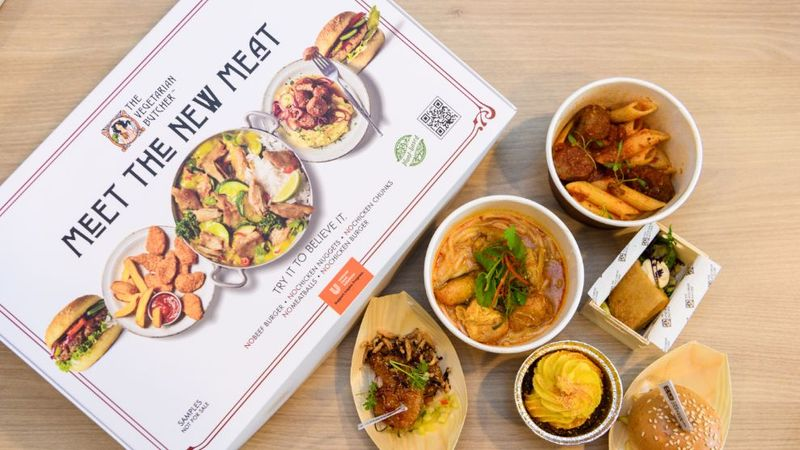 A box of The Vegetarian Butcher's NoChicken products laid out beside six dishes made with the plant-based protein