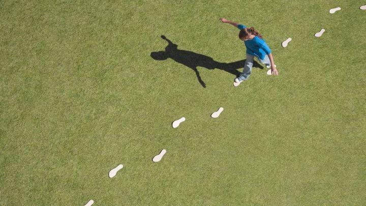 A woman walks on white footprints across a grassy field