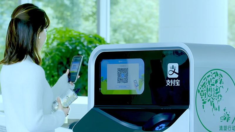 Woman holding plastic bottle ready to scan its QR code into an AI-enabled recycling and sorting machine.