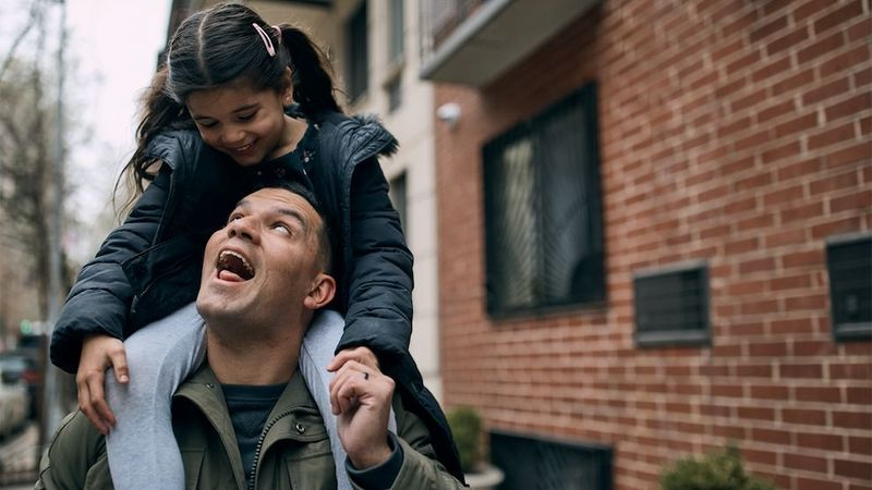 Father playing with daughter on his shoulders