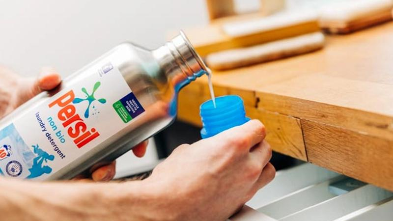 Person pouring Persil out of the new Loop stainless steel bottle