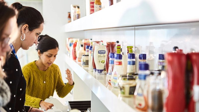 A number of Unilever employees selecting condiments in the Unilever canteen.