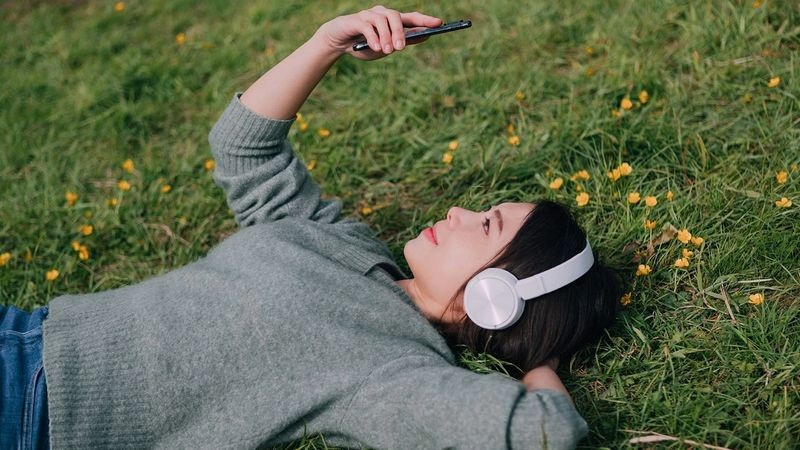 Young woman wearing headphones and studying phone, relaxes on a grassy field