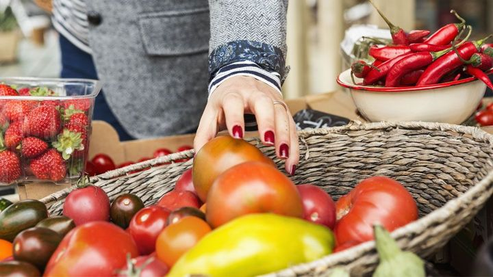 A womans hand reaching into a basket of vegetables