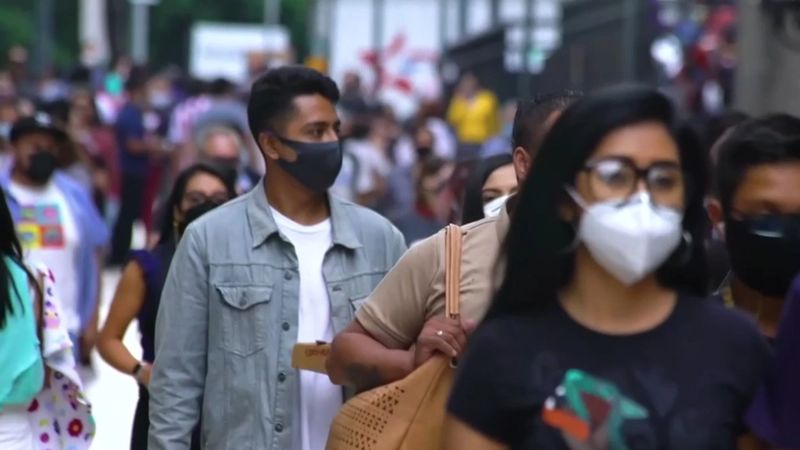 A busy street in Latin America with everyone wearing masks over their nose and mouth