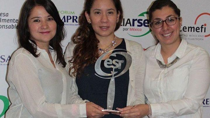 Tres mujeres sosteniendo un premio en sus manos.