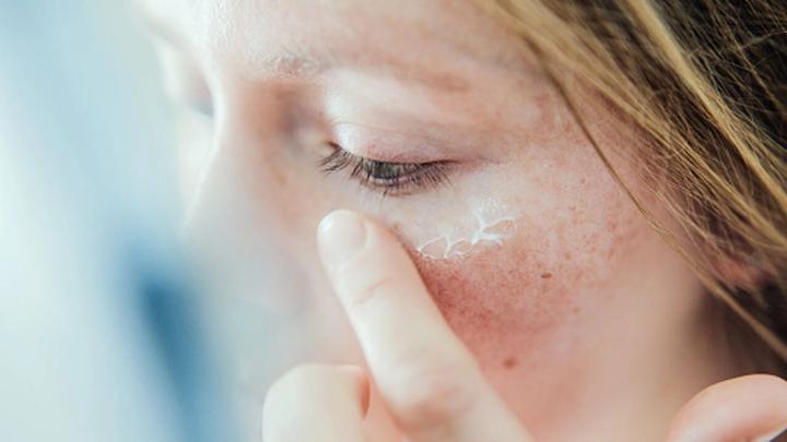 Tyttö-levittää-ihonhoitotuotetta-kasvoihin