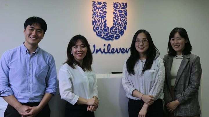 Unilever employees posing in front of Unilever logo