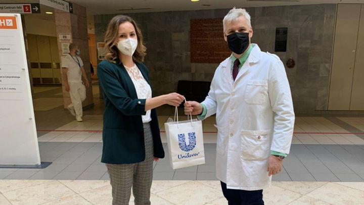 Az Unilever egyik munkatársa egy Unileveres ajándékcsomagot ad át a kórház egy dolgozójának.