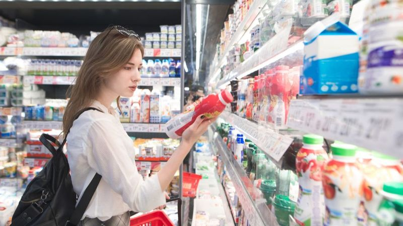 Woman in grocery store, holding a product and looking at its label.