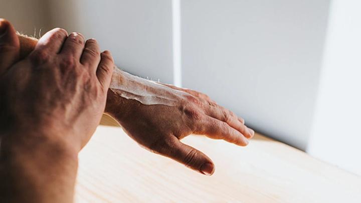 Hand rubbing cream into arm