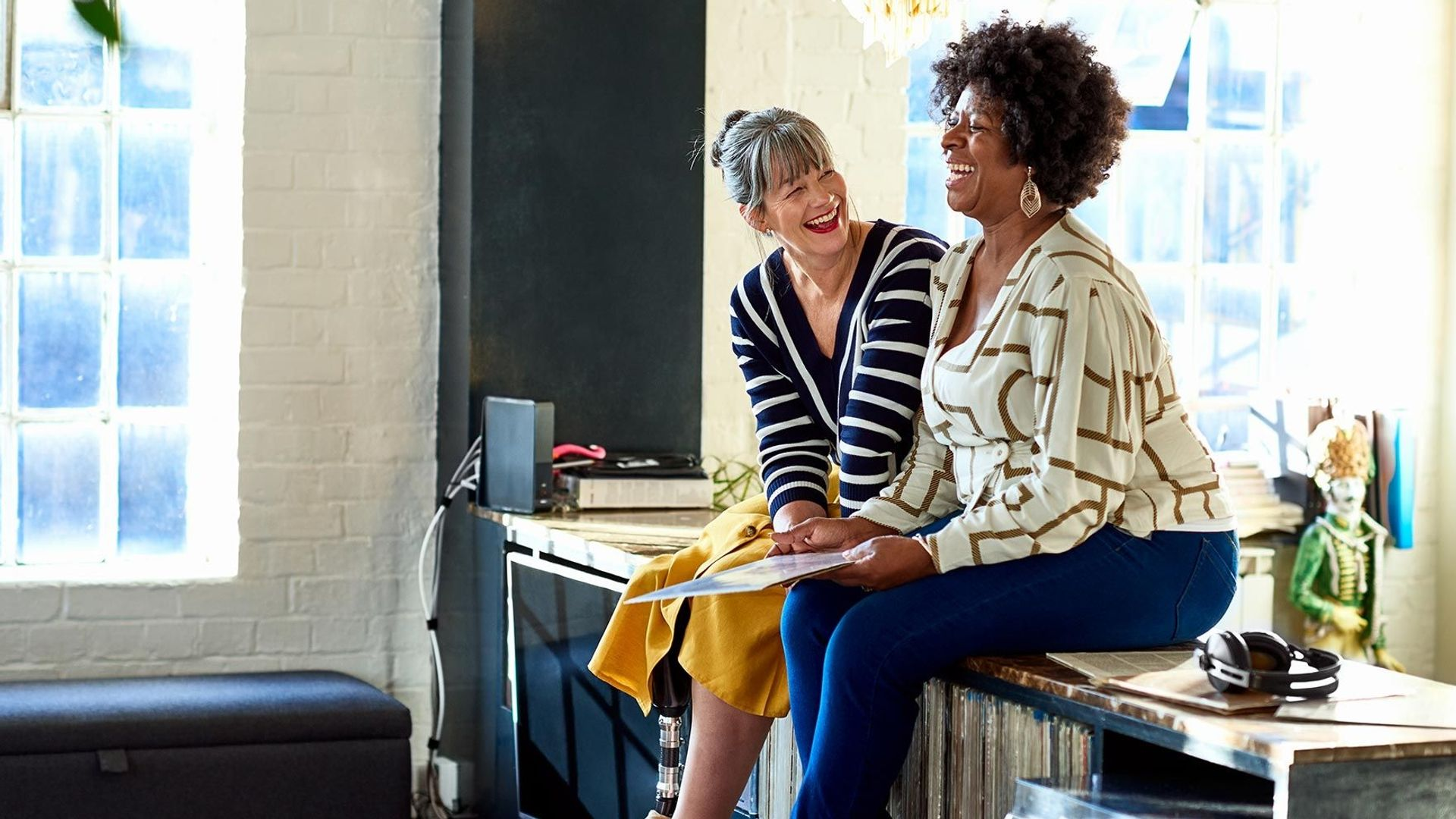 Two women laughing together while sitting on an office desk