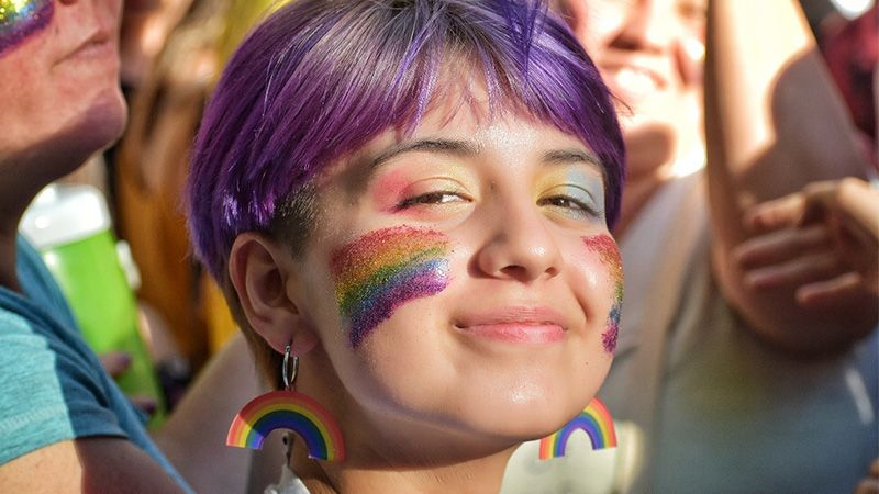 Smiling young woman with purple hair and pride rainbow facepaint and earrings
