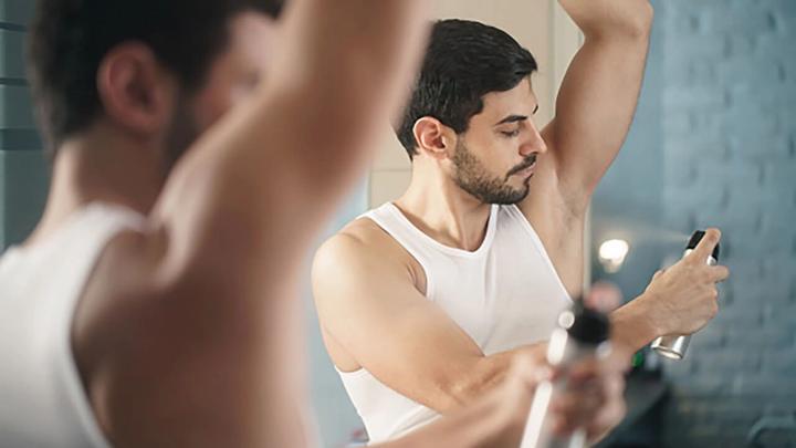 Mies-suihkuttaa-deodoranttia-kainaloon