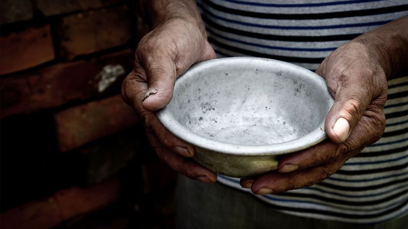 A pair of hands holding an empty food bowl