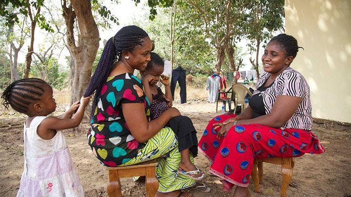 Afrikaanse vrouwen in kleurrijke kleding zitten buiten lachend tegenover elkaar.