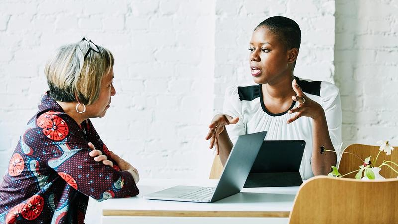 Two women in animated discussion over their laptops