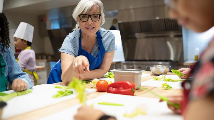 Woman in blue apron leaning over a kitchen counter