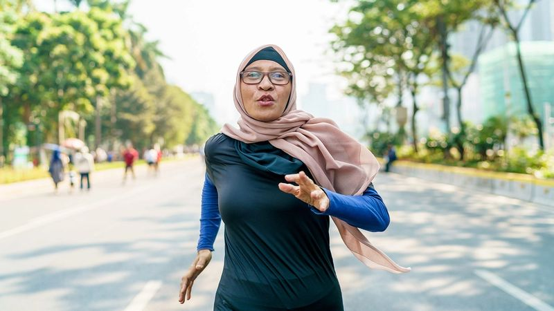 A woman in a headscarf jogging down a tree-lined road