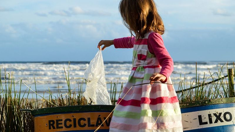 A young girl picks up a piece of plastic from some beside the sea