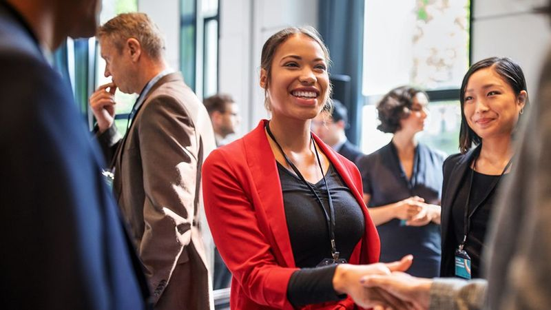 Businesswoman shaking hands. In 2020, Unilever reached its target of 50% of all managerial roles being held by women.