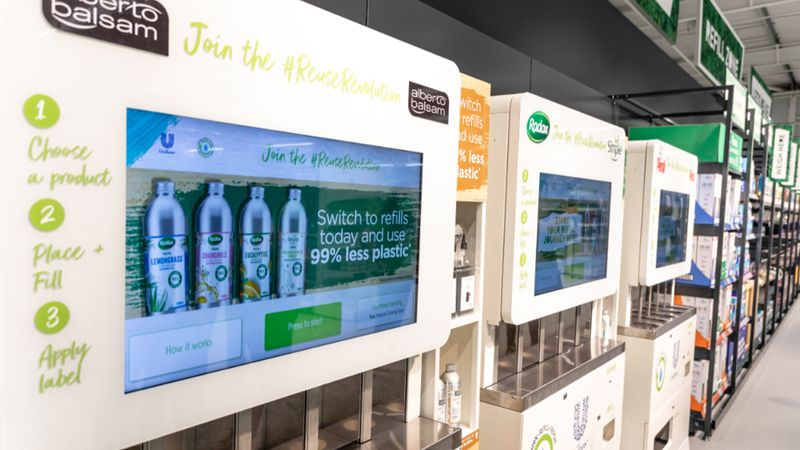 Three refill machines for Unilever brands lined up in the aisle of the Asda store in Leeds, UK.