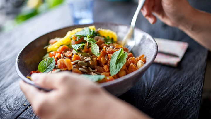 Hand holding a bowl of chickpeas and vegetables with mint