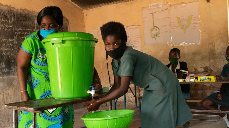 A green hand washing station is used by two women