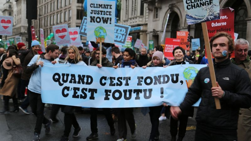 A ben & jerry's climate protest with people holding a sign saying Quand C'est Fondu, C'est Foutu!