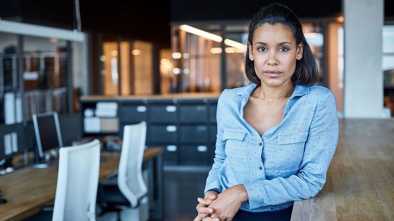 A woman stares confidently at the camera from an office
