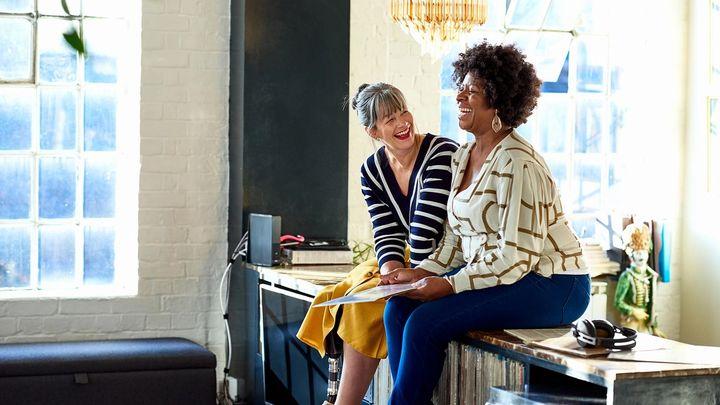 Two women sitting talking on a desk in an office