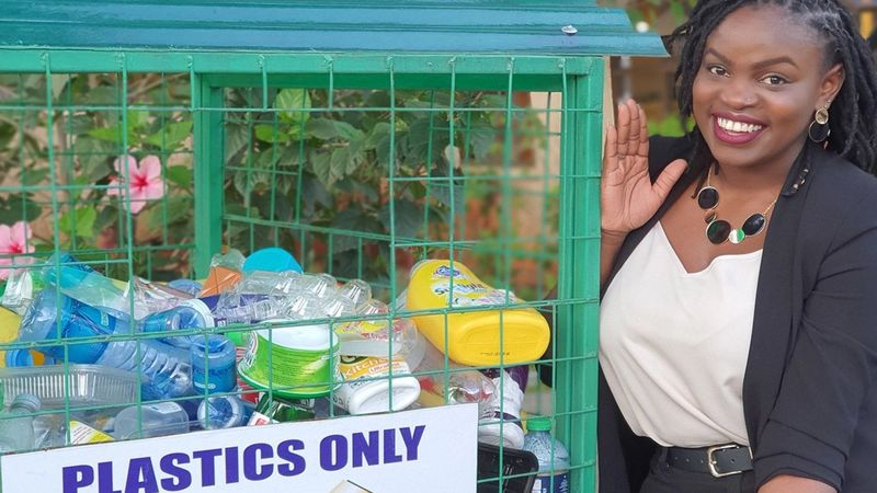 Unilever employee, Draganah Omwange stands next to a recycling bin. She set up this initiative to help reduce plastic waste