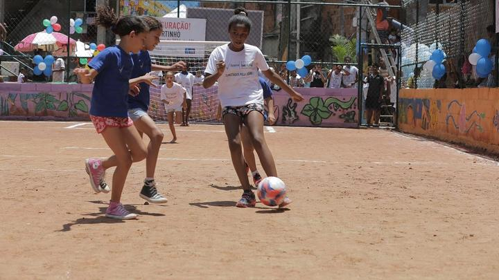 Girls playing football on an inner-city dirt pitch surrounded by fencing, being watched by a small group of people.