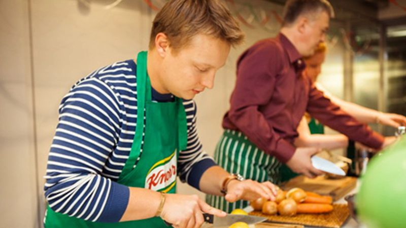 A young man wearing a Knorr apron chops vegetables as part of a cookery class