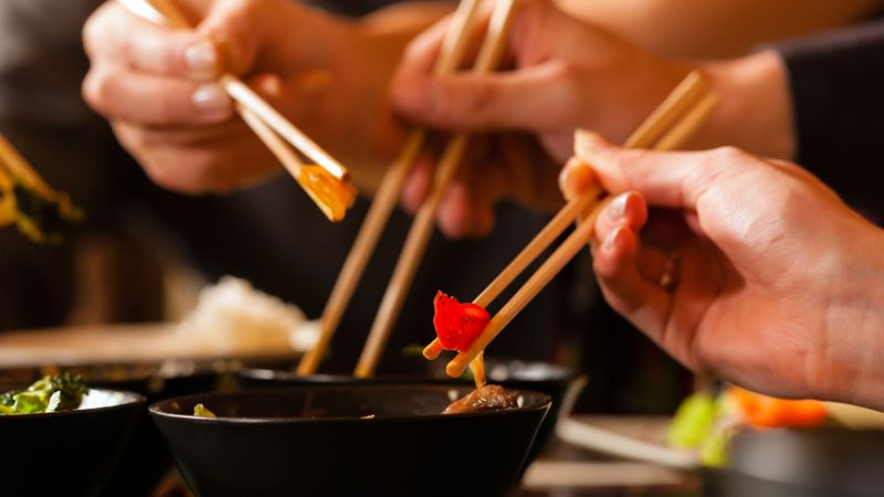 Two people eating with chopsticks from black bowls
